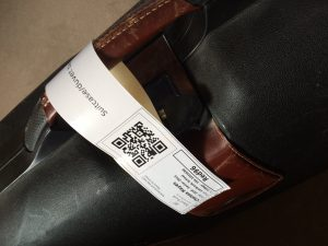 A suitcase with a QR code tracking label attached